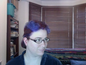 Head and shoulders of a woman with dyed purple hair with red stripes sprayed on.
